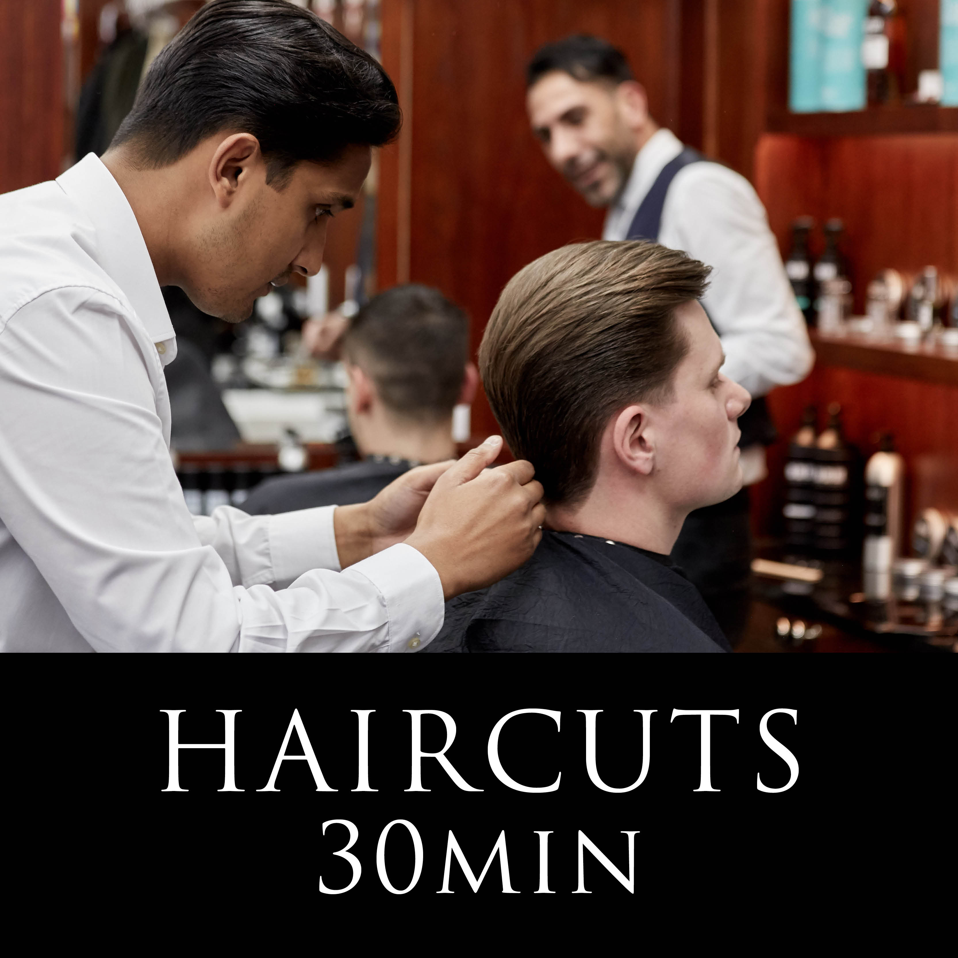 a man sitting down in a barber chair having his hair combed